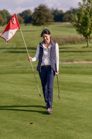 putt: Female golfer holding the flag from the hole in her hand as she removes it to make her final putt on the green standing smiling at the camera