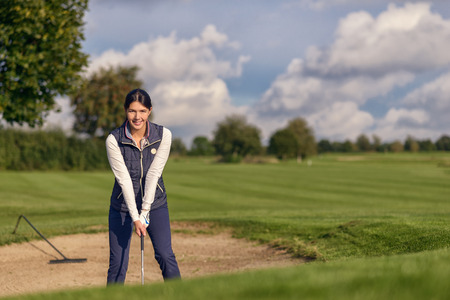 long sleeve: Young woman golfer standing in a sand bunker on a golf course with a club in her hand smiling at the camera as she tries to exit the sand Stock Photo