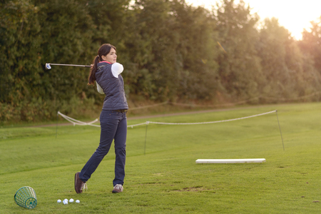 driving range: Female golfer standing on the driving range on a late afternoon day, standing in the finish position