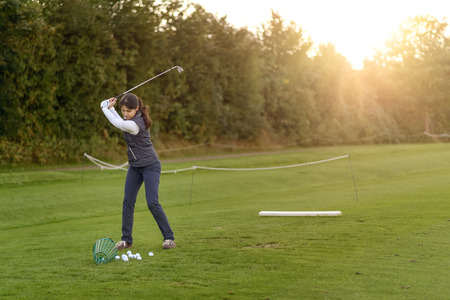 driving range: Female golfer standing on the driving range on a late afternoon day, concentrating while swining her club Stock Photo