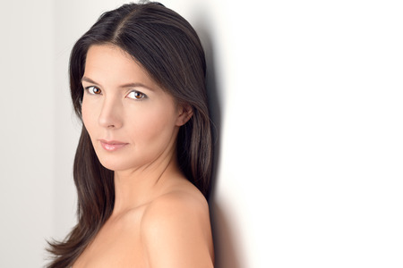 mojada: Mujer bastante joven en el vestido blanco Casual sonríe en la cámara mientras se inclina la espalda contra la pared, copia espacio a la derecha