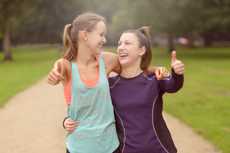 happy healthy woman: Half Body Shot of Two Happy Healthy Woman at the Park Showing Thumbs Up at the Camera After their Training. Stock Photo