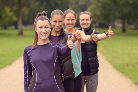 Four Happy Healthy Young Women in Line, Showing Thumbs Up at the Camera After their Outdoor Exercise.