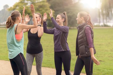 ダブル ハイファイブを与える 4 つの幸せな健康な女性は、公園での屋外運動後リラックスしながらジェスチャーします。 写真素材
