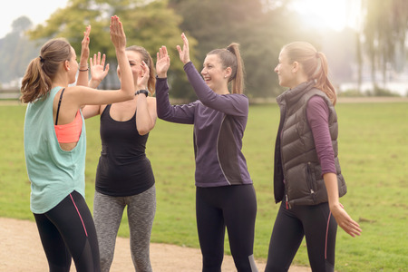 athletic women: Four Happy Healthy Women Giving Double High Five Gesture While Relaxing After an Outdoor Exercise at the Park. Stock Photo