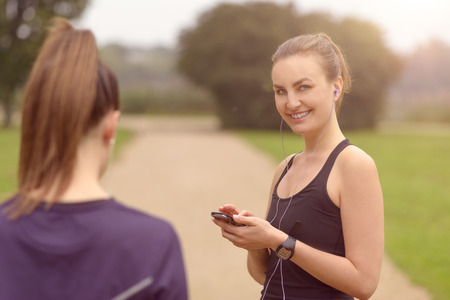 half body: Half Body Shot of a Healthy Young Woman with Headphones, Smiling at the Camera While Taking Rest After an Outdoor Exercise with her smartphone in her hands Stock Photo
