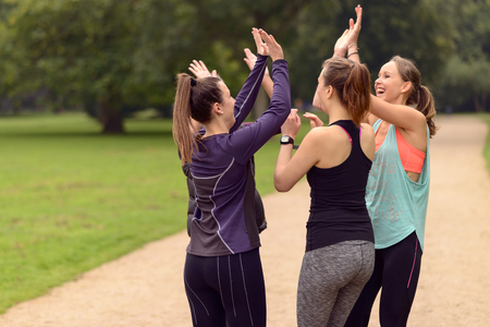 Four Happy Healthy Women Giving Double High Five Gesture While Relaxing After an Outdoor Exercise at the Park. Stock Photo