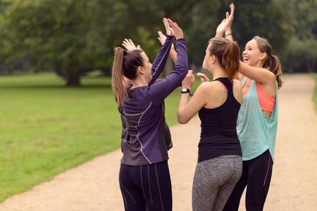 Quatro Feliz mulheres saudáveis ??Dar Duplo High Five Gesto Enquanto que relaxa após um exercício ao ar livre no parque.