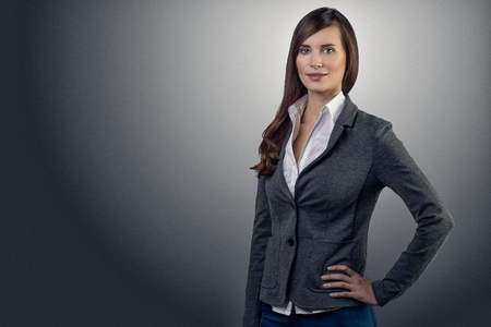 Stylish young businesswoman with a friendly expression looking directly at the camera, closeup of her face on a grey with copy space Archivio Fotografico