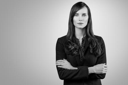 enigmatic: In bianco e nero, ritratto di una bella donna elegante professionale in piedi con le braccia piegate in una giacca elegante guardando la telecamera con un sorriso enigmatico, con spazio di copia