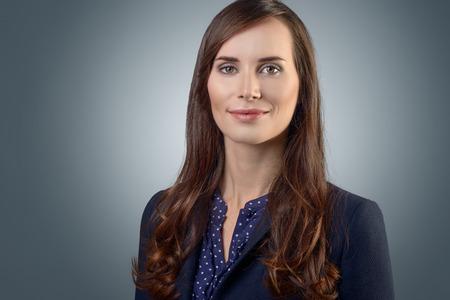 Stijlvolle jonge zakenvrouw met een vriendelijke uitdrukking direct kijken naar de camera, close-up van haar gezicht op een grijze met een kopie ruimte Stockfoto