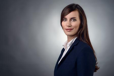 직접 카메라를 찾고 친화적 인 식 세련된 젊은 사업가, 복사 공간이 회색에 그녀의 얼굴의 근접 촬영