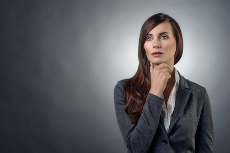 inscrutable: Thoughtful serious businesswoman with an inscrutable expression staring straight ahead with her hand to her chin, over grey with copy space