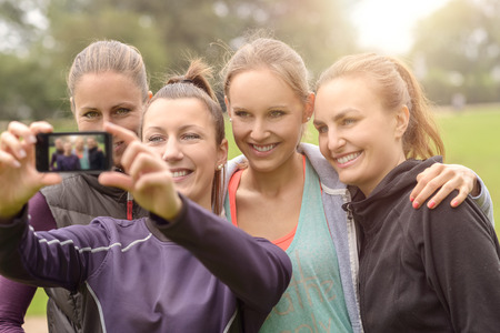 women sport: Half Body Shot of Four Happy Women Taking Selfie using smart Phone After Doing an Outdoor Physical Exercise at the Park. Stock Photo