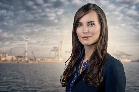 woman business suit: Attractive businesswoman with curly brown hair wearing a stylish jacket standing in front of a harbor or business port view smiling at the camera, upper body portrait
