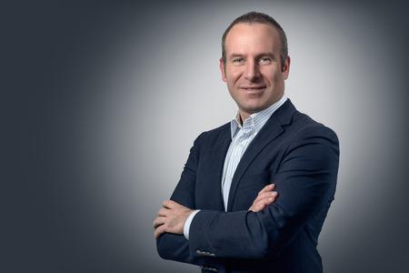 ejecutivos: Hombre de negocios con estilo hermoso de pie con los brazos cruzados mirando a la cámara con una expresión amable, sobre un fondo gris con espacio de copia Foto de archivo