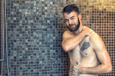 Friendly young man with a full beard standing soaping himself in the shower and smiling at the camera, upper body with copy space