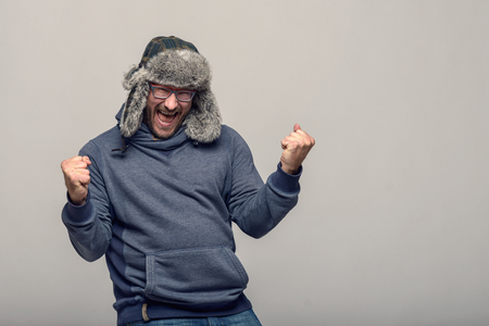 exultant: Happy man wearing glasses and a winter hat cheering and celebrating raising his clenched fists in the air with an exultant expression, over grey with copy space Stock Photo