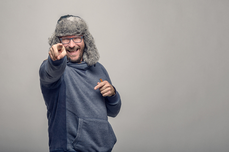 jovial: Laughing jovial man wearing glasses and a furry winter hat standing pointing at the camera with a playful expression, over grey with copyspace