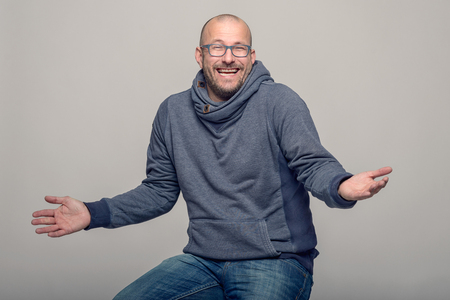 shrugging: Charismatic balding middle-aged man wearing glasses laughing and shrugging his shoulders to show his ignorance, seated upper body over grey