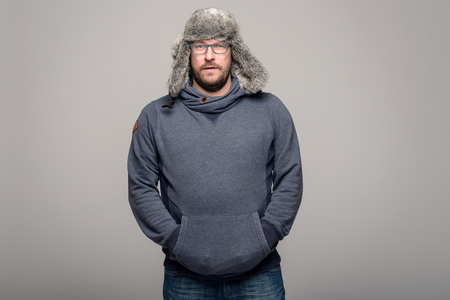 flaps: Serious attractive middle-aged man wearing glasses in winter fashion standing with his hand in the pouch on his warm top and wearing a warm furry hat with ear flaps, three-quarter over grey