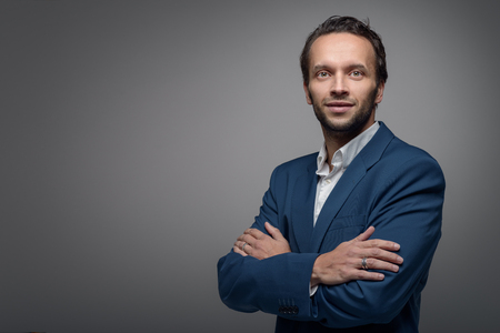 male face: Handsome stylish businessman standing with crossed arms looking at the camera with a friendly expression, on a grey background with copy space