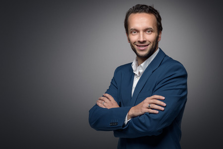 Handsome stylish businessman standing with crossed arms looking at the camera with a friendly expression, on a grey background with copy space