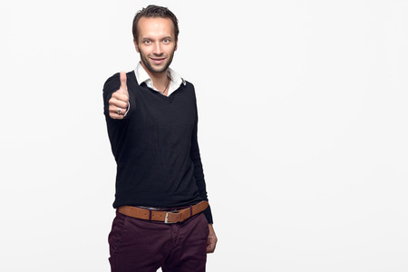 motivating: Happy young man giving thumbs up while looking at the camera, isolated with copy space