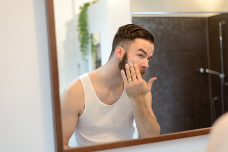 morning routine: Young man applying shaving cream above his beard, morning routine, a personal care and hygiene concept Stock Photo