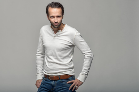 speculate: Attractive man standing with his hands on his hips peering directly at the camera with an intent speculative expression isolated over a grey background