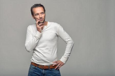 slim: Thoughtful attractive middle-aged man with his finger to his mouth standing looking towards blank copy space on a grey background Stock Photo