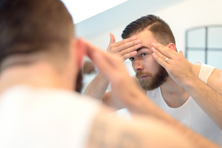 man rear view: Bearded man checking his complexion in the bathroom mirror, looking concerned, rear view over the shoulder.