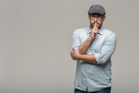 the finger: Hombre con gafas de mediana edad y una gorra de paño de pie con una expresión seria haciendo un gesto de shushing con el dedo a los labios pidiendo silencio, aislado en gris, con copia espacio