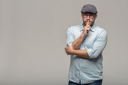 Middle-aged man wearing glasses and a cloth cap standing with a serious expression making a shushing gesture with his finger to his lips asking for silence, isolated on grey with copy space