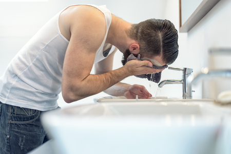 face: Bearded man rinsing his face in the bathroom under water from the tap in the hand basin after completing his shaving Stock Photo