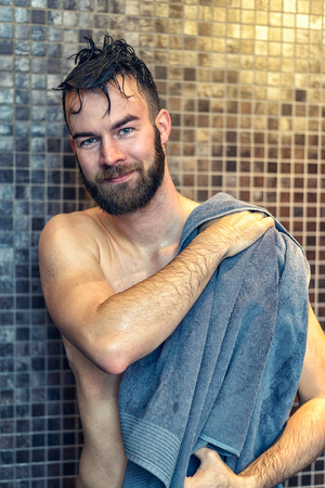 Handsome bearded young man drying himself with a towel after enjoying a shower in the bathroom, upper body smiling at the camera
