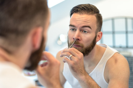 plucking: Handsome bearded young man standing plucking his nasal hairs in front of the mirror in the bathroom during his daily grooming