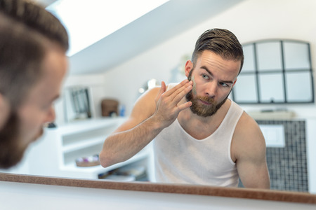 bearded: reflection in the bathroom mirror of a young bearded man applying a face mask to his skin in a skincare and hygiene concept