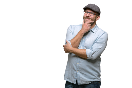 contemplative: Thoughtful middle-aged man in a cap and glasses standing with his hand to his chin staring into the air with a contemplative expression, isolated on white with copy space Stock Photo