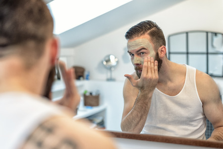 reflection in the bathroom mirror of a young bearded man applying a face mask to his skin in a skincare and hygiene concept