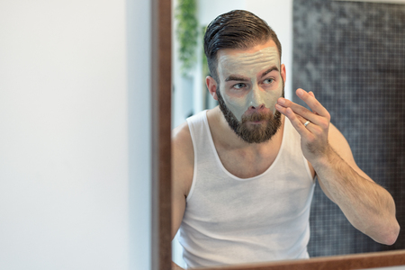 antifaz: reflejo en el espejo del ba�o de un hombre barbudo joven de aplicar una mascarilla para la piel en un concepto de cuidado de la piel y la higiene Foto de archivo