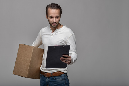 acknowledge: Smiling handsome courier delivering a parcel to the door of a house holding out a clipboard for signature to acknowledge receipt, on grey background