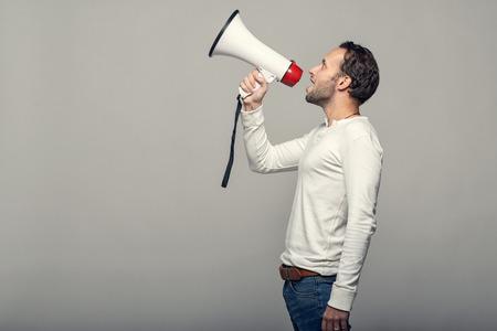megafono: Hombre hablando por un meg�fono como �l hace un discurso p�blico, participa en una protesta o organiza una manifestaci�n o promoci�n, sobre gris, con copia espacio en el lado