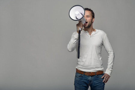 he is public: Man speaking over a megaphone as he makes a public address, participates in a protest or organises a rally or promotion, over grey with copy space to the side