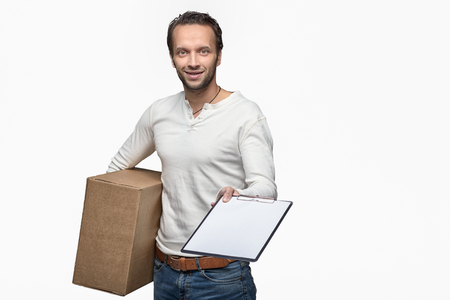 acknowledge: Smiling handsome courier delivering a parcel to the door of a house holding out a clipboard for signature to acknowledge receipt, isolated on white Stock Photo