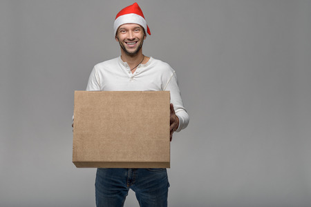 delivery box: Cheerful attractive young man in a Santa Hat carrying or delivering a large brown cardboard box for Christmas, over grey with copy space Stock Photo