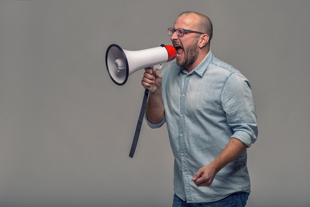 public address: Man speaking over a megaphone as he makes a public address, participates in a protest or organises a rally or promotion, over grey with copy space to the side