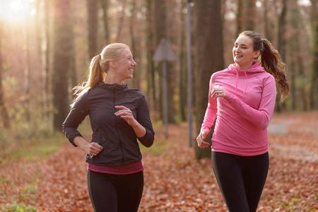 mujeres corriendo: Dos atractivas señoritas ajuste a trotar juntos a través de un bosque de otoño en el chat, ya que correr a través de los árboles, en un estilo de vida saludable y el deporte concepto