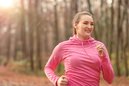 approaching: Pretty fit young woman jogging through autumn or fall woodland approaching the camera, close up upper body portrait in a healthy lifestyle concept