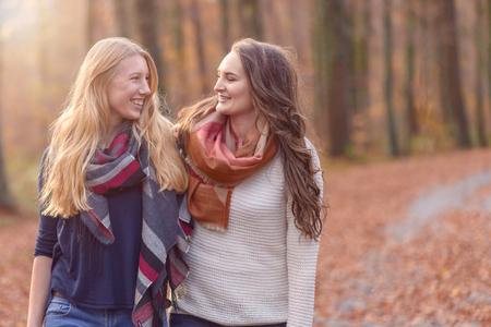 Twee aantrekkelijke jonge vrouwelijke vrienden lopen arm in de arm door de herfst bos met elkaar chatten en glimlachen elkaar, close-up bovenlichaam bekijken